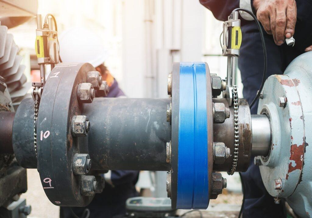 Servicetekniker justerar pumpen och elmotorn på plats